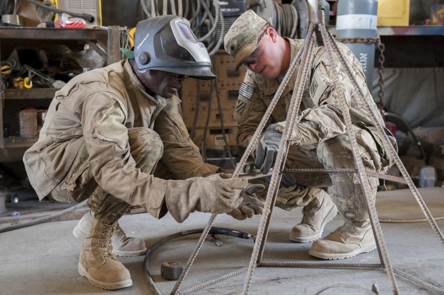Sgt. Patrick Lewis, left, a Queens, N.Y., native and an allied trade specialist, levels a piece of rebar that will reinforce a culvert denial system, with the help of Spc. Jonathan Carpenter, a Pendleton, S.C., native and a wheeled vehicle mechanic, both in Company B, 703rd Brigade Support Battalion, 4th Infantry Brigade Combat Team, 3rd Infantry Division, at Forward Operating Base Shank, Afghanistan, June 11, 2013. The system will be used to prevent extremists from placing improvised explosive devices in culverts in Wardak Province, Afghanistan, along Highway 1, a main road to Kabul, preventing military and civilian casualties.