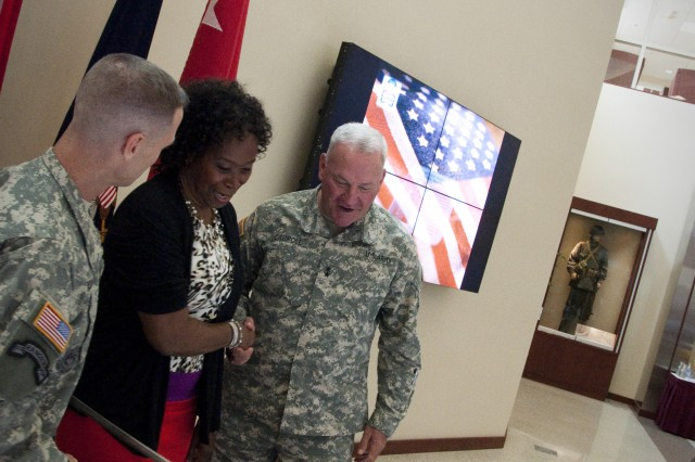 Command Sgt. Maj. Christopher K. Greca (left) and Maj. Gen. Leslie J. Carroll (right), the U.S. Army Forces Command command sergeant major and chief of staff, respectively, cut the command's 40th birthday cake alongside Maria Lewis, the command's longest-serving civilian employee, during a ceremony July 1, 2013 in the Marshall Hall atrium on Fort Bragg, N.C. (U.S. Army photo by Dave Chace, FORSCOM Public Affairs)