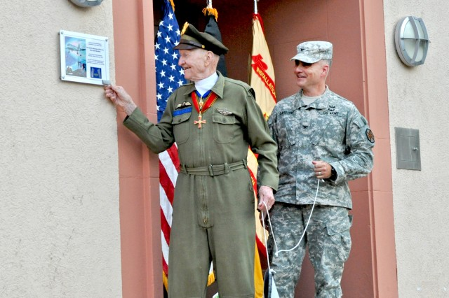 Retired Col. Gail Halvorsen and Col. David Carstens unveil a plaque on the Berlin Airlift pilot's fomrer barracks on Clay Kaserne, Germany, June 27, 2013.