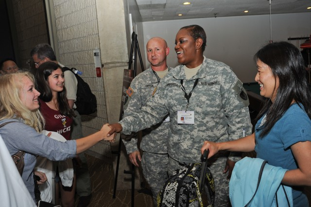 LEESBURG, Va. -- Staff Sgt. Tracy Campbell, RDECOM, greets eCYBERMISSION finalist teams as they arrive for the National Judging and Educational Event June 17. Sgt. Joshua Geren, RDECOM communications and electronics center, looks on.