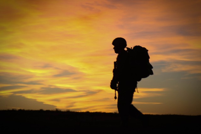 As the sun rises June 27, a Soldier hikes along the 12-mile road march course during the Expert Infantryman Badge testing hosted by the 4th IBCT, 1st Inf. Div., at Fort Riley.  The 12-mile march is the final event infantrymen must complete before earning their EIB.