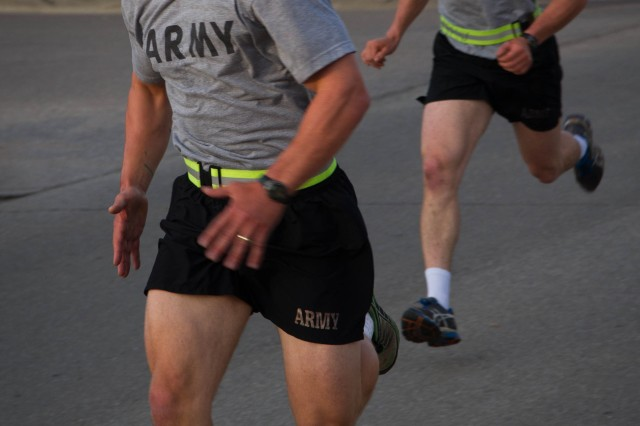 First Lt. Christopher Siok (left) and 1st Lt. Samuel Gulland (right) sprint to the finish to complete the 2-mile run portion of the Army Physical Fitness Test during the Expert Infantryman Badge testing June 22 at Fort Riley. The APFT is the first event infantrymen are required to complete on their way to earning their EIB.