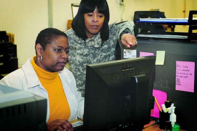 Chief Warrant Officer 2 Monica Bolton mentors Nekoletta Brown, a logistics management intern specialist assigned to the Ft. Carson, Colo., Mission Support Element Logistics Office.