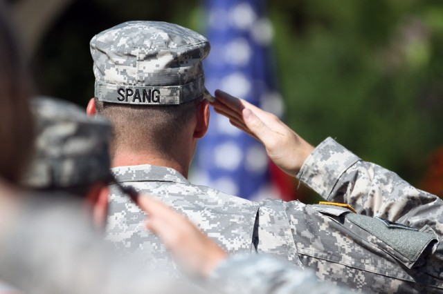 "FORT SAM HOUSTON, Texas - Spc. Matthew Spang, combat engineer, 95th Engineer Company, 65th Engineer Battalion, 130th Engineer Brigade, salutes the American flag during the playing of the national anthem July 1 at the beginning of his Purple Heart ceremony. Spang, who claims Colorado Springs, Colo., as his hometown, was presented two Purple Hearts "" for wounds on two separate incidents "" during the ceremony at the Warrior and Family Support Center Purple Heart Courtyard."