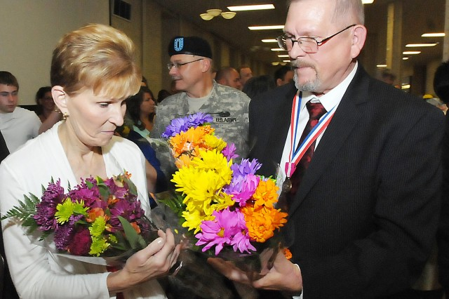 Newly retired Dennis Durham presents his wife, Ilene, with flowers following the retirement ceremony. Durham retired with 44 years of federal service. (Photo by Jon Micheal Connor, ASC Public Affairs)