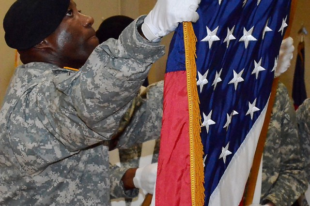 Sgt. 1st Class Curtis Benjamin, ASC, takes part in the retirement ceremony by assisting the color guard in the retreat ceremony by casing the U.S. flag (Photo by Elizabeth Adolphi, ASC Public Affairs)