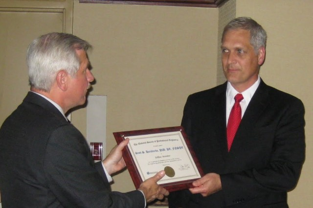 National Society of Professional Engineers Vice President Harve Hnatiuk (left) presents Crane Army Ammunition Activity Director of Manufacturing and Engineering Dr. Scott Haraburda with his certificate as a Fellow of the Society.