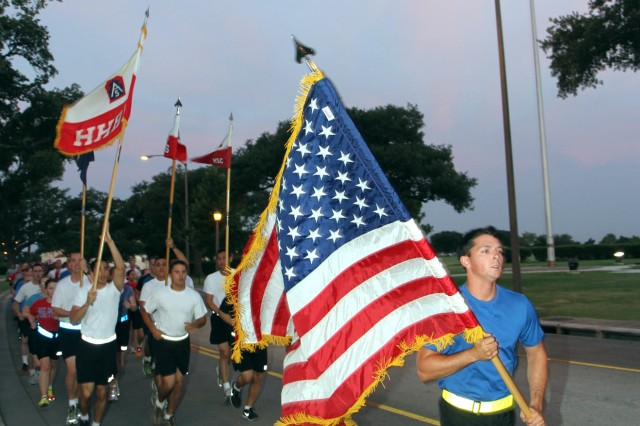 FORT SAM HOUSTON, Texas - The Soldiers of U.S. Army North (Fifth Army) conduct an early celebration of Independence Day with a morning run around post July 3. As a show of patriotism, the Soldiers wore red, white or blue t-shirts during the run. Sgt. Benjamin Roberts, Headquarters Support Company, Headquarters and Headquarters Battalion, U.S. Army North, leads the way with the American flag. Roberts is assigned to the Army North caisson section.