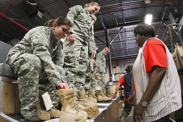 New Soldiers try on their Army Combat Uniforms, known as ACUs, the ACU-Alternate uniform, boots and other equipment during reception, June 20, 2013, at the Central Initial Issue Point at Fort Sill, Okla., before going to Basic Combat Training.