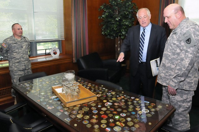 Illinois Gov. Pat Quinn points to a coin in Maj. Gen. John Wharton's office as ASC Command Sgt. Maj. James Spencer looks on July 1. (Photo by Jon Micheal Connor, ASC Public Affairs)