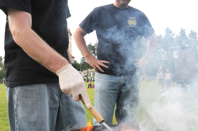 Chief Warrant Officer 3 Philip Wolfe of B Troop, Regimental Support Squadron, 2nd Cavalry Regiment (left), and Chief Warrant Officer 3 Charlie Hillyer, JMTC OMA maintenance technician, sizzle burgers to perfection during USAG Grafenwoehr's Fourth of July celebration.