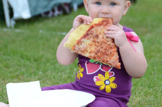 Ryliah Hill, 17 months old, shows a slice of pizza who's boss at the Grafenwoehr community Fourth of July celebration.