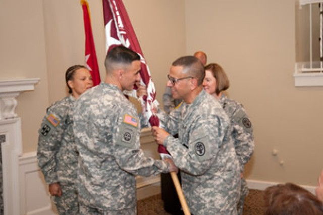 Incoming Commander of Kirk U.S. Army Health Clinic Lt. Col. David Zinnante accepts the guidon from the Commander of Fort George G. Meade U.S. Army Medical Activity and Kimbrough Ambulatory Care Center Col. Danny B.N. Jaghab during the June 26 change of command ceremony at the Top of the Bay.