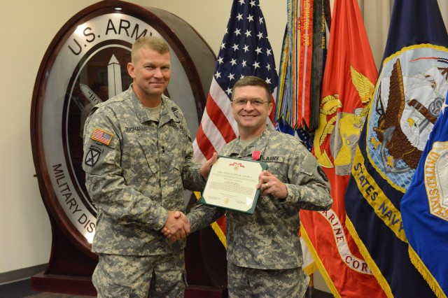 Col. Corey L. Bradley smiles with Maj. Gen. Jeffrey S. Buchanan, commander, Joint Force Headquarters - National Capital Region and the U.S. Army Military District of Washington after receiving the Legion of Merit medal during a ceremony held at Fort McNair, July 3, 2013.