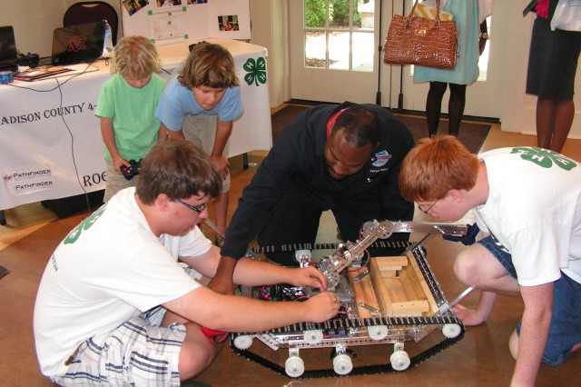 Dr. Patrick Taylor, center, an engineer at the Aviation and Missile Research Development and Engineering Center, explains robotic principles to Madison County 4-H Robotics team members during the Tennessee Valley Jazz Society's Science and Arts Symposium. Thursday's event was part of the 27th Tennessee Valley Jazz-N-June Festival held June 15-23.
