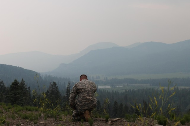 First Lt. Justin Cowan, chaplain, prays during a visit to Guard members in the area of West Fork Complex fire Colorado National Guard operations, June 30, 2013.
