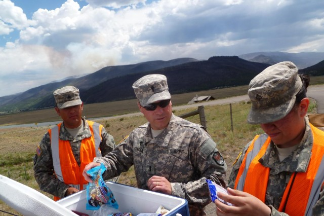First Lt. Justin Cowan, chaplain, hands out cookies made by his wife, Melanie, to Guard members in the area of West Fork Complex fire Colorado National Guard operations, June 30, 2013.