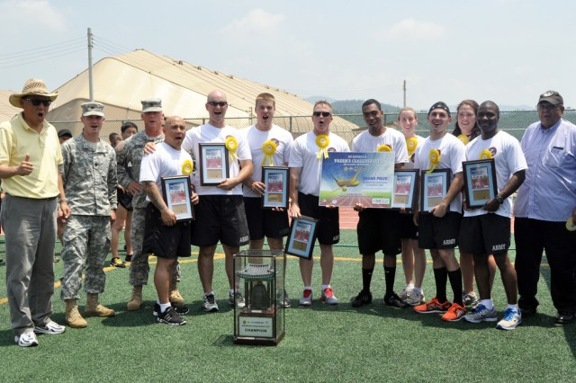 The first place team, the Wildcards, Lt. Col. Brian E. Walsh, Command Sgt. Maj. Lawrence D. Dougherty and DFMWR Paul Robinson pose with the team's prize, a Korean bell and the airline ticket to anywhere in Asia at the K-16 Warrior Challenge Cup, June 28. (U.S. Army photo by Pvt. Jung Young Ho)