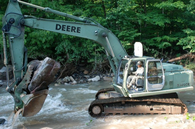 Pfc. Joshua Haller, a member of the New York Army National Guard's 827th Engineer Company, uses a hydraulic excavator to remove a boulder and other flood debris from Fulmer Creek, N.Y., July 3, 2013. About 24 hours after being called up by New York Gov. Andrew Cuomo, Soldiers of the unit, based in Horseheads, N.Y., began removing flood debris from Fulmer Creek and Fords Creek, to stabilize the streams and prevent further flood damage. The Soldiers also restored Fords Creek to its pre-flood course, increased its flow, and cleared debris from a mile-long section of Fulmer Creek. Haller is from Odessa, N.Y.