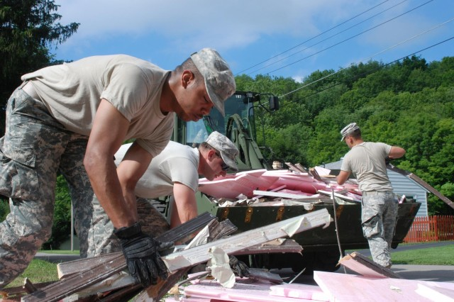 New York Army National Guard Soldiers Pfc. Trey Hubbard (left), Spc. Jason Briggs (middle) and Spc. Brandon Demeree dump flood-damaged property into the bucket of a front-end loader operated by Sgt. John Johnson, July 5, 2013, in Mohawk Valley, N.Y. Johnson belongs to the Buffalo-based 152nd Engineer Company, and the other Soldiers belong to the 206th Military Police Company, which is based in Latham, N.Y. The units were among those called up to provide humanitarian assistance to flood victims, and to clear flood debris from waterways in towns like Fort Plain, N.Y. and German Flatts, N.Y. Soldiers of the 206th Military Police company, aided by troops from the 152nd and 827th Engineer Companies, helped clean out and dispose of flood debris from about 150 homes by July 7. Johnson is from Stockton, N.Y.; Hubbard is from Utica, N.Y.; Briggs is from Canton, N.Y.; Demeree is from Little Falls, N.Y.