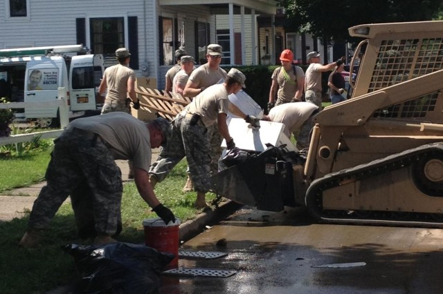 New York Army National Guard Soldiers from Task Force Engineer, a mixed force comprised of forces of the 204th Engineer Battalion, 206th Military Police Company, and 1427th Transportation Company, assist with debris removal in the community, July 5, 2013, following the Guard's recovery support to flash flooding in the Mohawk Valley. The National Guard's initial response force of more than 50 Soldiers, June 28, grew to some 250 Soldiers by July 3, to support local communities in their recovery.