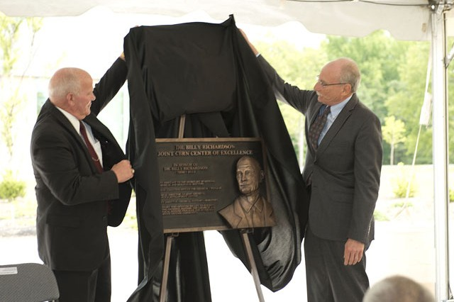 (From left) Douglas Bryce, Deputy Joint Program Executive Officer for Chemical and Biological Defense, and Mike Parker of Science Applications International Corporation, Inc. unveil the plaque dedicating the Joint CBRN Center of Excellence building to Dr. Billy Richardson during the  dedication ceremony held July 1.