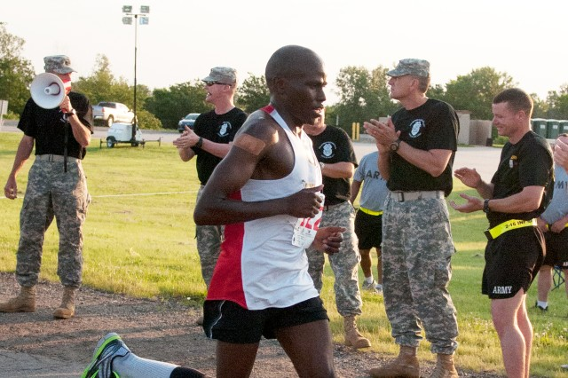 "Spc. Mathew Chesang, 1st Squadron, 6th Cavalry Regiment, Combat Aviation Brigade, 1st Infantry Division, crosses the finish line first during the ""Big Red One's"" Victory Week 10-Miler on June 12 at Fort Riley, Kan. The division hosts Victory Week each year to celebrate its and the Army's birthday. The Victory Week 10-Miler drew more than 300 runners, and was a qualifying event for the upcoming Army 10-Miler in Washington, D.C."