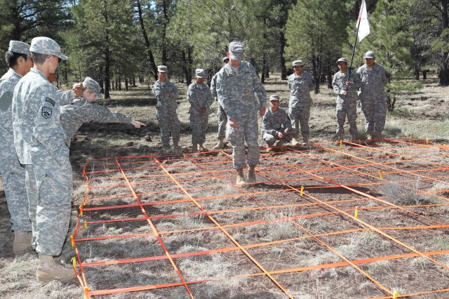 Tylor Whitehat, the cadet Command Sgt. Maj. of the Coconino Junior Senior High School Army JROTC unit, follows silent commands as he negotiates a simulated mine field at the 2013 JROTC cadet Leadership Challenge at Camp Navajo, Bellemont, Ariz.