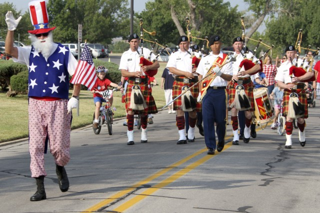 """A parade of families pulling kids in wagons, kids riding bikes and """"Costello's Own"""" playing bagpipes all follow Uncle Sam, who led the parade up Randolph Road, to begin the 4th of July ceremony outside McNair Hall here."""