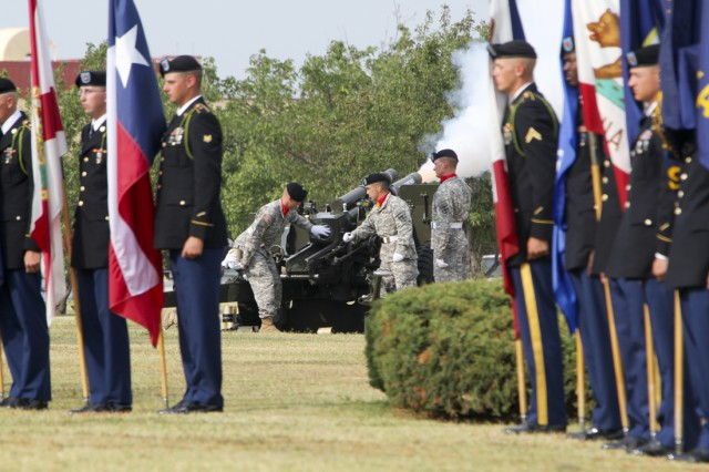 """During a salute to the nation, as a part of the 4th of July ceremony outside McNair Hall here, Soldiers hold all 50 state and U.S. territory flags, raising each one-by-one, while field artillerymen from B Battery, 2nd Battalion, 2nd Field Artillery, the """"Big Deuce,"""" fired a 105mm howitzer for each state."""