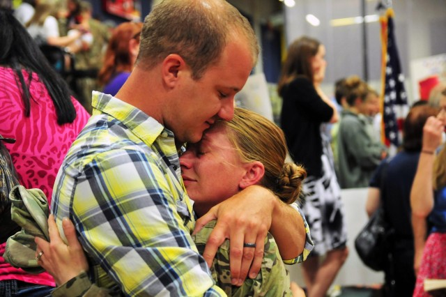 Spc. Jessie Nelson, an all-source intelligence analyst with Headquarters and Headquarters Company, 4th Stryker Brigade Combat Team, 2nd Infantry Division, hugs her husband, Matt, July 10 at Soldiers Field House on Joint Base Lewis-McChord, Wash. Nelson and approximately 230 4th SBCT soldiers returned home after an eight-month deployment to Afghanistan in support of Operation Enduring Freedom. (U.S. Army photo by Sgt. Kimberly Hackbarth, 4th SBCT, 2nd ID Public Affairs Office)