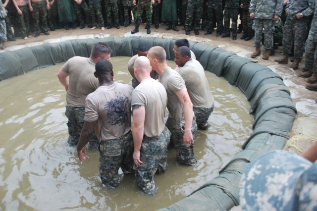 Soldiers from the 41st Signal Battalion, 1st Singal Brigade, move into the fighting pit filled with four-feet of water to compete in the eight-on-eight, winner takes all, wrestling event against  Soldiers from the Republic of Korean Army 60th Signal Battalion in Guri City, South Korea July 2, 2013.
