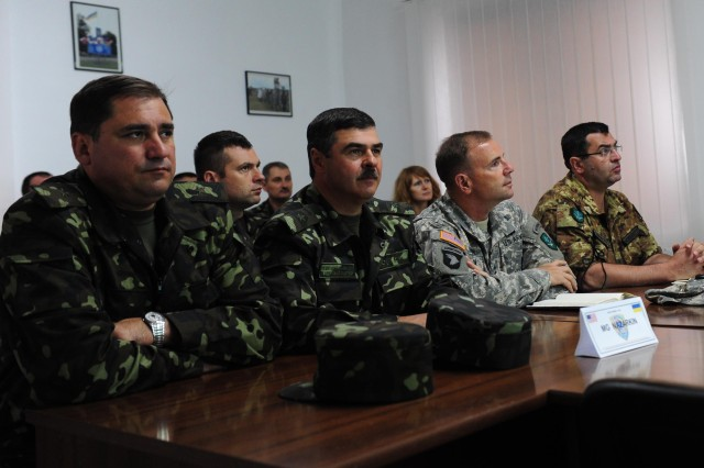 NATO Allied Land Command Commanding General Lt. Gen. Ben Hodges (middle right) receives a briefing alongside Rapid Trident's exercise director Ukrainian Army Maj. Gen. Vyacheslav Nazarkin (middle left) and Ukrainian Maj. Gen. Victor Ganushak, acting commander of the Western Operational Command, July 15, 2013, during Hodges' visit at Yavoriv, Ukraine. The purpose of Hodges visit was to gain an understanding of Ukraine's land forces capabilities and to observe multinational training. Rapid Trident 2013 is a U.S. Army Europe-led, multinational field training and command post exercise occurring at the International Peacekeeping and Security Center in the Ukraine, July 8-19, that involves approximately 1,300 troops from 17 nations. The exercise is designed to enhance interoperability between forces and promote regional stability and security.