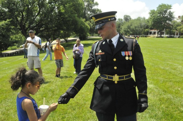 Eight-year-old Sonja Banks of Hammond, Ind., accepts a medal from Presidential Salute Battery Watchman Spc. Hollis Taylor following the 50-gun salute to the nation on Whipple Field July 4. Sonja is the daughter of former Old Guard Soldier Mark Banks. The 3d U.S. Infantry (The Old Guard) Presidential Salute Battery fired a round to salute each of the 50 states. The 50-gun firing, which honors the signing of the Declaration of Independence, is a 236 year-old tradition. For more photos from the Fourth of July celebration on JBM-HH, visit www.flickr.com/photos/jbm-hh/sets.
