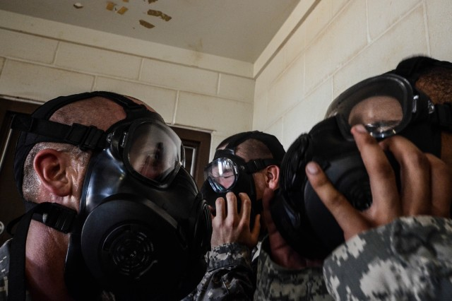 Drill Sergeant Mathew Tucker (left)  assigned to E Company 3rd Battalion 10th Infantry Regiment checks to make sure Soldiers break the seal of their mask inside the gas chamber on July 8, 2013 on Fort Leonard Wood MO. The Soldiers are exposed to CS gas to build confidence in their M50 series gas mask. (U.S. Army photo by Staff Sgt. Ronald Shaw Jr.)(Released)