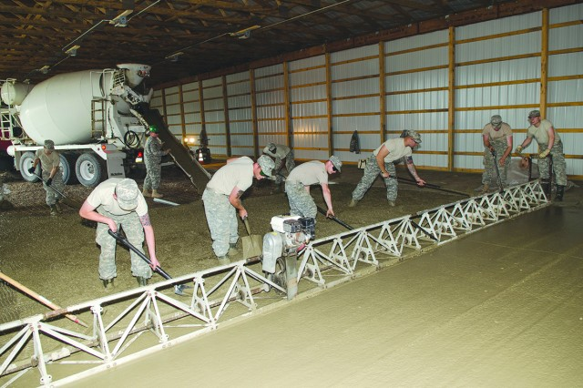 A team of carpenter/masons work together to distribute concrete as it flows from the truck just before it is pulled in front of a power screed.  The screed vibrates the concrete into the forms.  A Soldier moves the screed forward using a hand crank and cable system.
