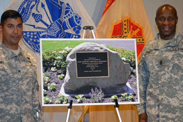 Col. Eluyn Gines (left), U.S. Army Garrison Fort Hamilton, N.Y., commander, and Command Sgt. Maj. Hector A. Prince (right), U.S. Army Garrison Fort Hamilton senior enlisted adviser, pictured with the stone dedicated as a permanent reminder at the Fort Hamilton Bluff of firefighter and U.S. Army National Guard Soldier Staff Sgt. Chris Engeldrum. Engeldrum, 39, of the 69th Infantry Regiment New York Army National Guard, was killed when his vehicle hit an improvised explosive device while on patrol outside of Baghdad, Nov. 29, 2004.