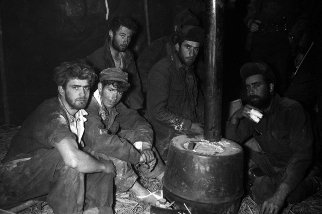 American and Australian prisoners of war warming up before a stove in the 24th Division medical clearing station after being returned to U.S. lines by Chinese Communists, February 10, 1951.