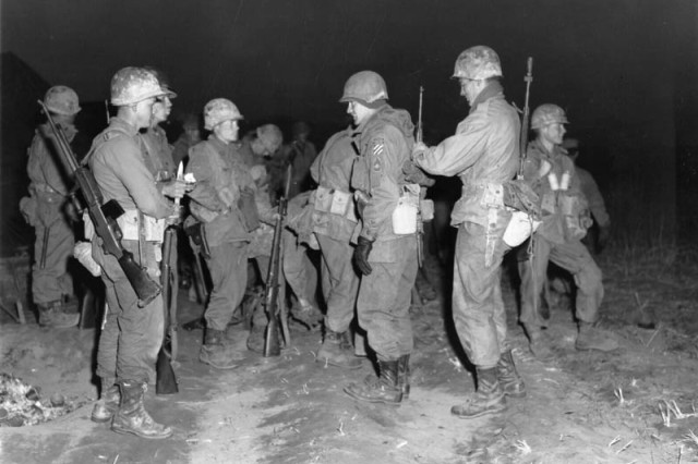 Men of the 3rd Ranger Company, 3nd Infantry Division, adjust their gear before undertaking a dawn patrol across the Imjin River, Korea April 17, 1951.
