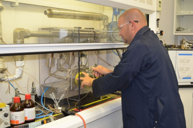 Steven Gray, chemical engineer at the Quality Evaluation Facility, does a test setup for the C2A1 canister using a gas chromatograph.