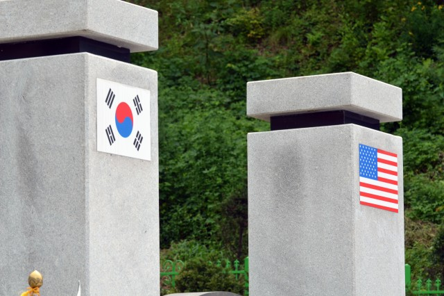 "CAMP HUMPHREYS, South Korea "" The Korean and American flags are displayed on the top of the columns of The Splendor of Peace and Freedom monument located near Jochiwon, South Korea."