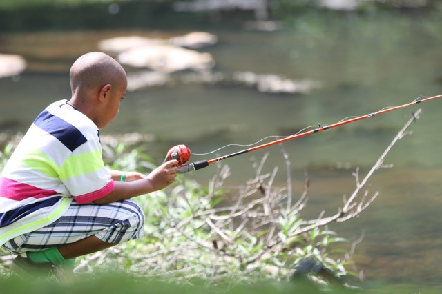 Camper Apollo Kim, 8, enjoys a peaceful moment fishing July 10, at Fort Campbell, Ky. The goal of the Fort Campbell Survivors Outreach Services Camp SOS is for the children to have a week of fun. (U.S. Army photo by Sgt. Leejay Lockhart, 101st Sustainment Brigade Public Affairs)