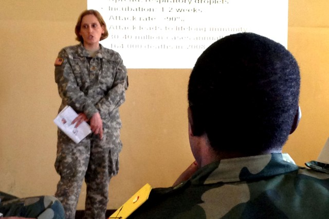 Maj. Kelly Mann gives a briefing on measles for Congolese doctors during Medical Readiness and Training Exercise 13-3.  Eight Soldiers traveled from as far away as Montana and Oklahoma to participate in the exercise. They are experts in fields as diverse as tropical medicine and logistics to public healthcare and clinical lab operations.  U.S. Soldiers participating in the exercise represented both Active and Reserve components of the U.S. Army. The goal of this training is to reinforce the capabilities of Congolese medical professionals, strengthen the relationship between Congolese and U.S. professionals, as well as providing training for U.S. personnel.