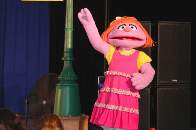 Katie, a character representing the child of a military family, greets the crowd as she steps onstage for the first time during the Sesame Street / USO Experience for Military Families performance.
