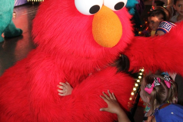 Elmo gives a lucky attendee a big furry hug during the Sesame Street / USO Experience for Military Families performance.