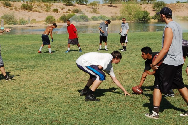 Staff Sgt. Timothy O'Hara has the Desert Hills Cougars offense practicing passing drills during a summer practice.