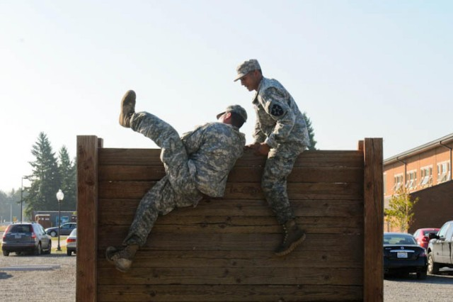 U.S. Army soldiers hurdle over an obstacle during the 7th Infantry Division's Ranger School Assessment on Joint Base Lewis-McChord July 9, 2013. The course helped prepare Soldiers for the demands of Army Ranger School. (U.S. Army photo by Sgt. Zachary Gardner/Released)