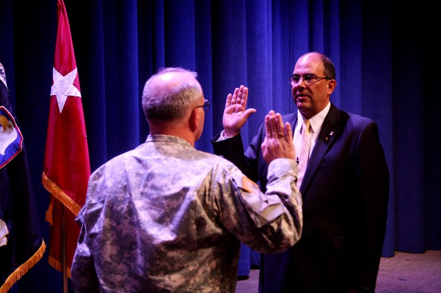 Lt. Gen. Richard P. Formica, commanding general, U.S. Army Space and Missile Defense Command/Army Forces Strategic Command, administers the oath to Thomas E. Webber, acting director of SMDC's Technical Center, and director of the Technical Center's Space and Cyberspace Directorate, during Webber's promotion to the senior executive service at the Von Braun III auditorium July 16.