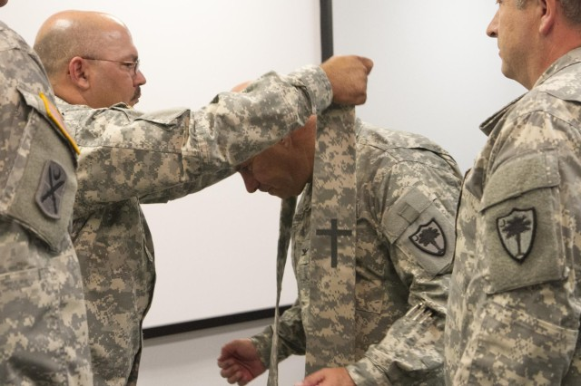 U.S. Army Master Sgt. Dennis Reynolds, South Carolina Army National Guard chaplain assistant, places the stole on Col. Steven Shugart, the outgoing  Carolina Army National Guard chaplain, during a ceremony at the adjutant general's office in Columbia, S.C., July 13, 2013.  (U.S. Army National Guard photo by Sgt. Erica Knight/Released)