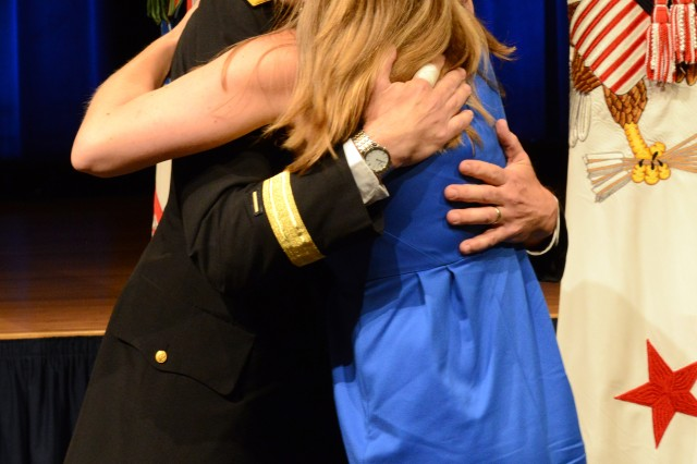 Lt. Gen. Thomas W. Spoehr hugs his daughter Catherine after she affixes his new rank on his uniform.